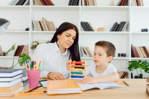 Частный репетитор-женщина помогает молодому студенту с домашним заданием за столом в яркой детской комнате
