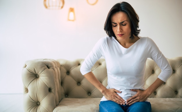 Female problems. adult woman is sitting on a sofa at home and touching her lower stomach while suffering from cramps.
