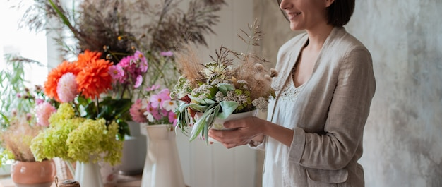Female professional florist prepares the arrangement of wild flowers.