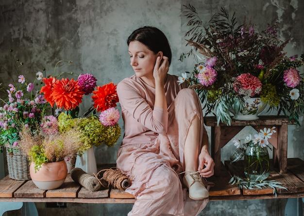 野生の花のアレンジメントを準備する女性専門の花屋。