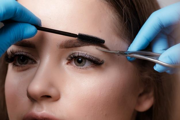 Female профессиональный парикмахер, обслуживающий клиента, стригу брови ножницами.