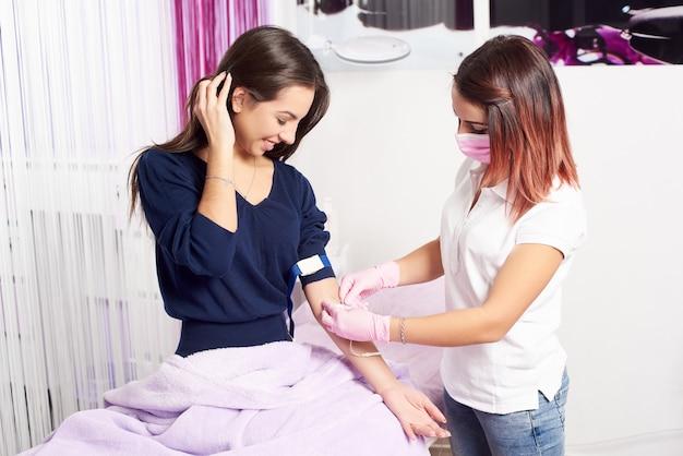 Женский профессионал красоты берет кровь для анализа от красивой брюнетки-клиента.