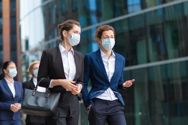 オフィススーツとマスクを身に着けている女性の専門家が会議を行い、市内で一緒に歩き、話し、プロジェクトについて話し合っています。ミディアムショット。パンデミックとビジネスコンセプト