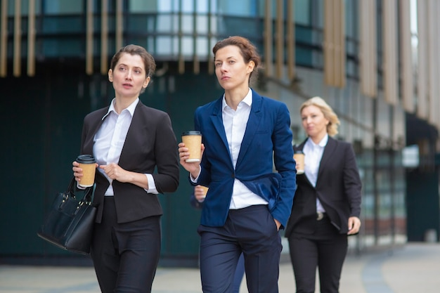 Female professionals with paper coffee cups wearing office suits, walking together in city, talking, discussing project or chatting. front view. businesswomen outdoors concept