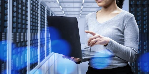 Женский программист с компьютерным ноутбуком в серверной комнате