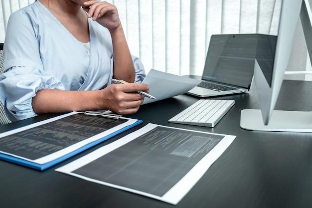 Itオフィスのソフトウェアjavascriptコンピューターで働いている女性プログラマー、コードとデータコードのwebサイトを作成し、データベーステクノロジをコーディングして問題の解決策を見つけます。