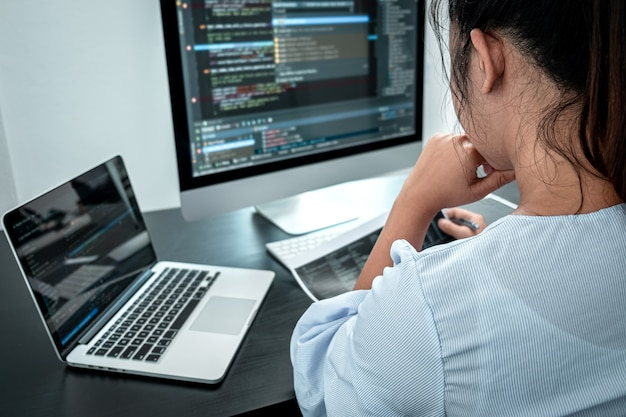 Female programmer working in software javascript computer in it office