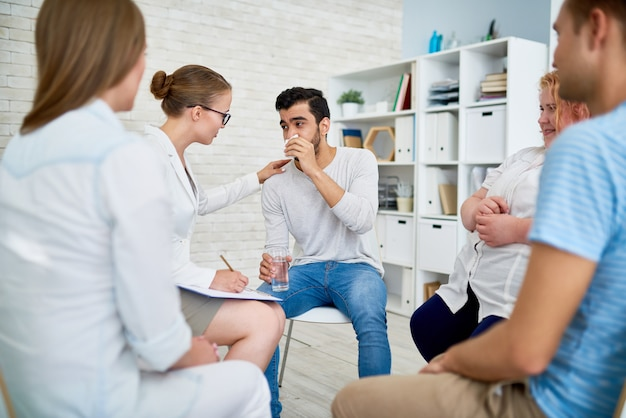Female psychiatrist consulting young man in group session