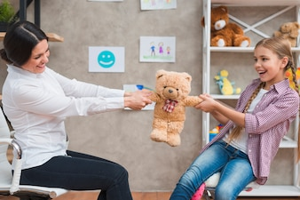 Female psychologist and smiling girl sitting face to face pulling the teddybear