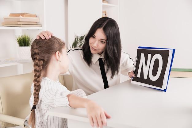 Женский психолог консультирует маленькую девочку в кабинете.