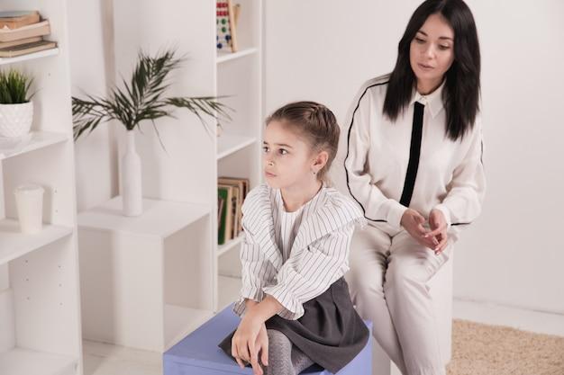 여성 심리학자는 캐비닛에 있는 어린 소녀를 상담합니다.