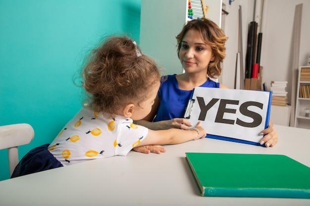 Женский психолог консультирует маленькую девочку в кабинете