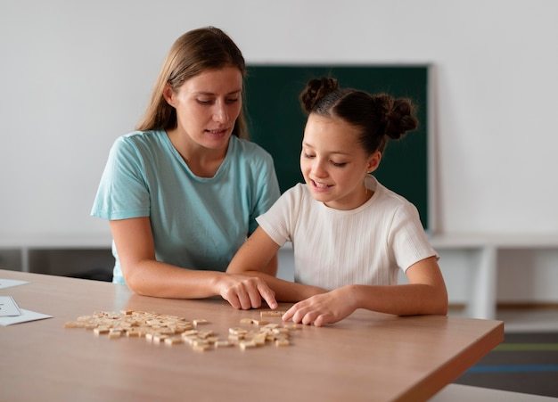 언어 치료에서 소녀를 돕는 여성 심리학자