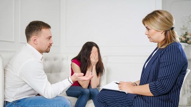 걱정된 젊은 부부를 돕는 여성 심리학자. 가족치료. 화난 사람들