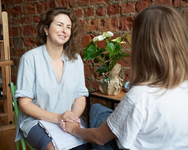 女性の心理学者が女性の手を握って、コーチのノートへの書き込み。