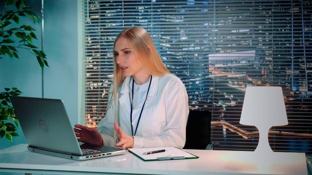 白衣を着た女性心理学者が、コンピューターに座って患者とオンラインビデオ相談を行っています...