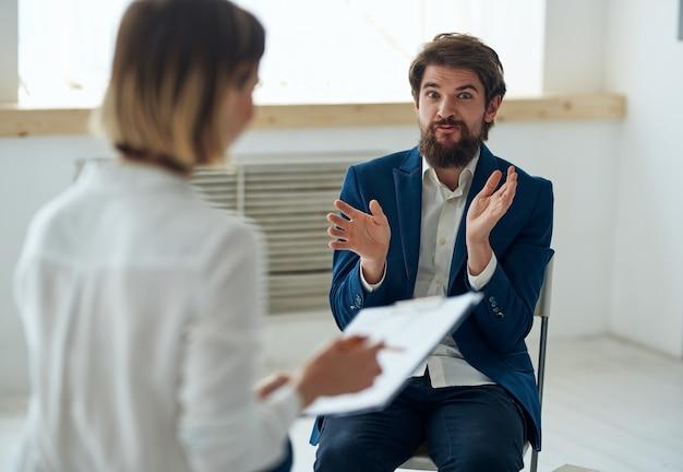 Женский психолог рядом с пациентом коммуникативной терапии стресса