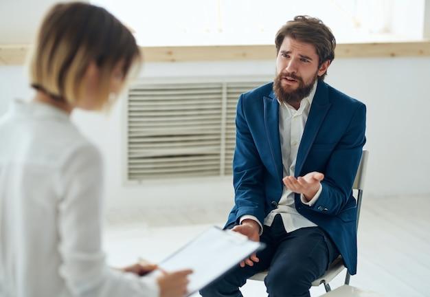 患者のコミュニケーション療法のストレスの隣にある女性心理学者