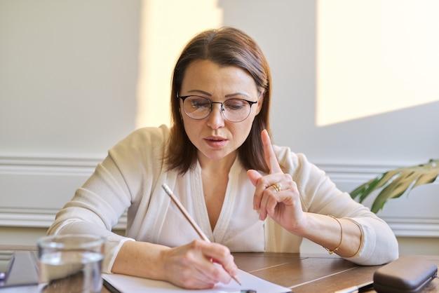 Female psychologist, psychiatrist looking at webcam of digital tablet