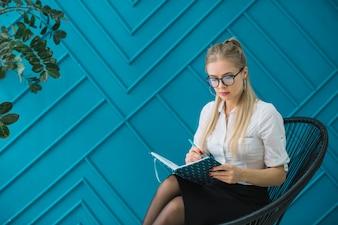 Женский психолог сидя против сочинительства стены дизайна голубого на дневнике с ручкой
