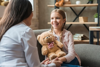 Female psychologist talking with girl holding teddy bear during therapy session