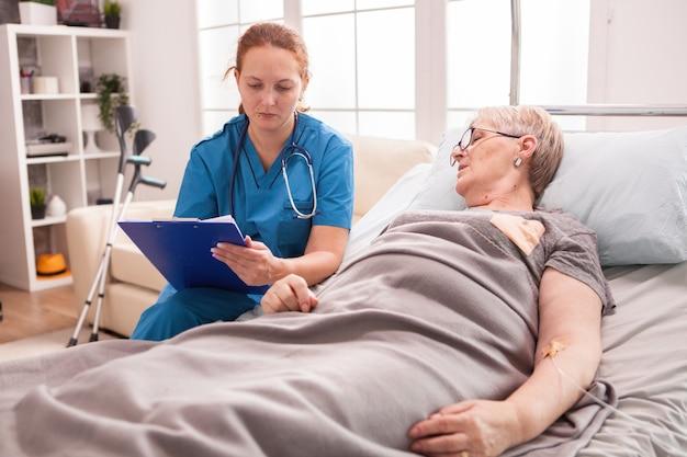 여성 심리학자는 요양원에서 수석 여성과 이야기하고 있습니다.
