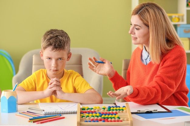 自閉症に苦しんでいる男の子と一緒に働く女性心理学者