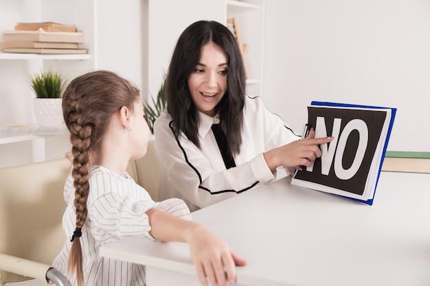 흰색 캐비닛에 있는 소녀와 함께 일하는 여성 심리학자.