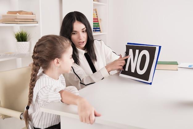 白いキャビネットで女の子と一緒に働く女性心理学者。