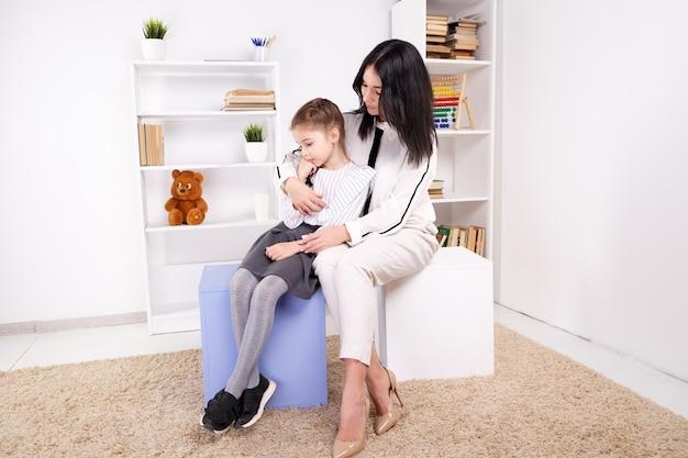 Женский психолог, работающий с девушкой в белом кабинете.