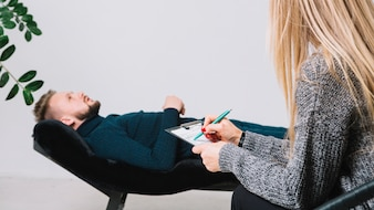 Female psychologist writing notes on clipboard in front of patient lying on couch in clinic