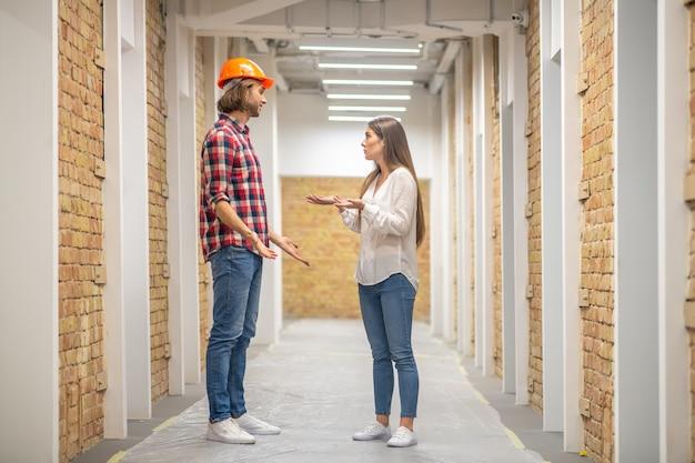 Женщина-покупатель обсуждает вопросы строительства с рабочим