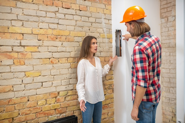 Female purchaser talking to the construction worker and looking unpleased