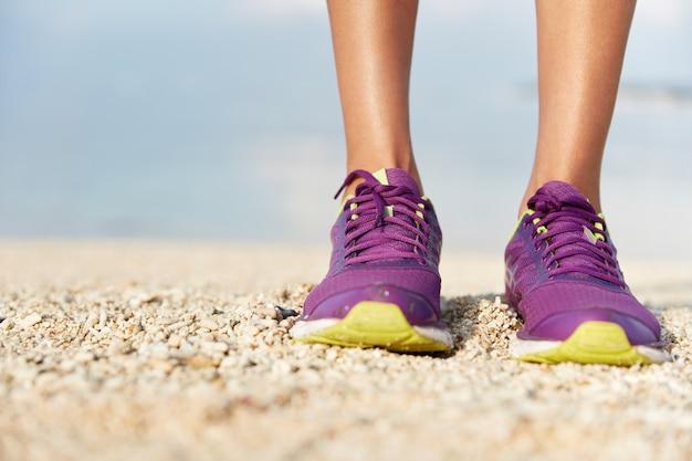 女性の紫のスニーカーはシェルビーチに立って、スポーツの靴を履いています。スポーツと健康的なライフスタイルのコンセプト