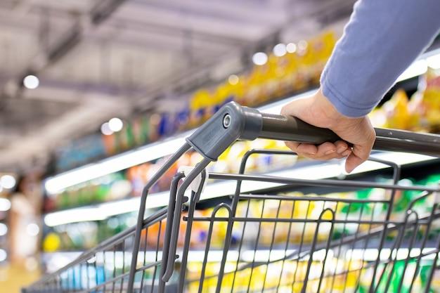Женщина толкает тележку покупок в супермаркете