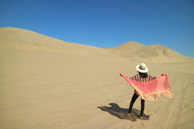 Female putting on her scarf on windy day at huacachina desert in ica region of peru, south