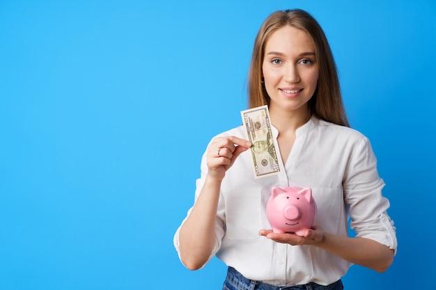 Женщина кладет деньги в розовую копилку на синем фоне