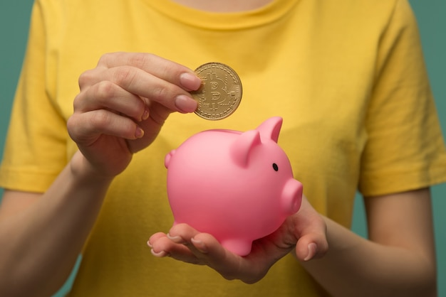 Female putting physical bitcoin into piggy bank, investment in cryptocurrency concept.