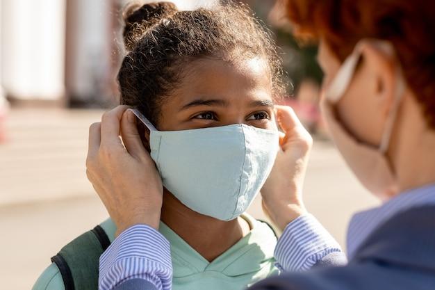 혼혈 수양 딸의 얼굴에 보호 마스크를 씌운 여성