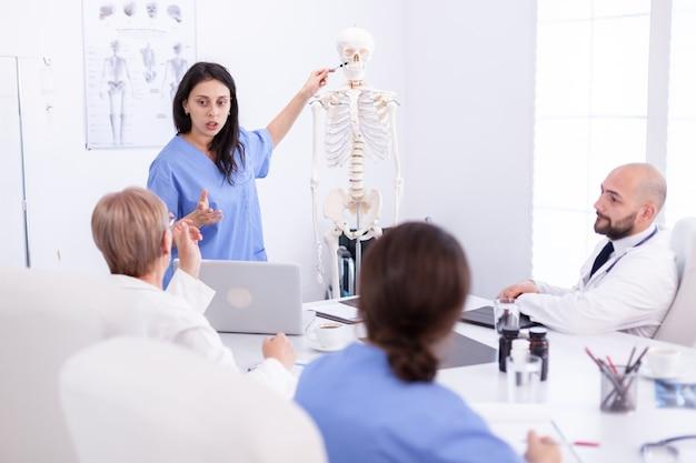 医療スタッフの前でスケルトンを使用してプレゼンテーションを行う女性放射線科医。病気について同僚と話しているクリニックの専門家セラピスト、医学の専門家