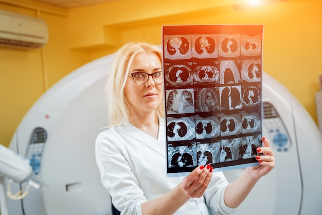 Female radiologist looking at x-ray in the room of computed tomography.