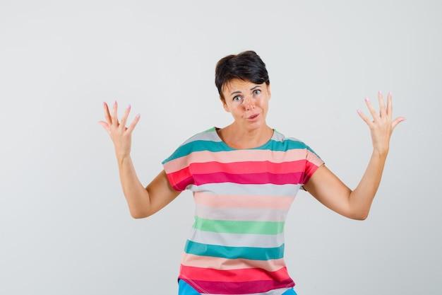 Женщина поднимает руки в полосатой футболке и выглядит смущенной. передний план.