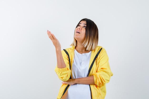 Женщина поднимает руку, глядя вверх в футболке, куртке и выглядит изумленно, вид спереди.
