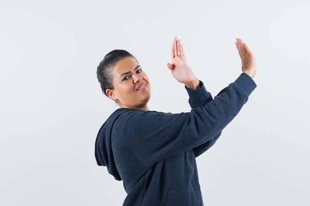 パーカーで身を守るために手を上げて自信を持っている女性。