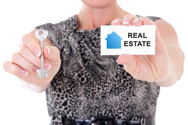 Female real estate agent hands holding key and visiting card isolated on white background