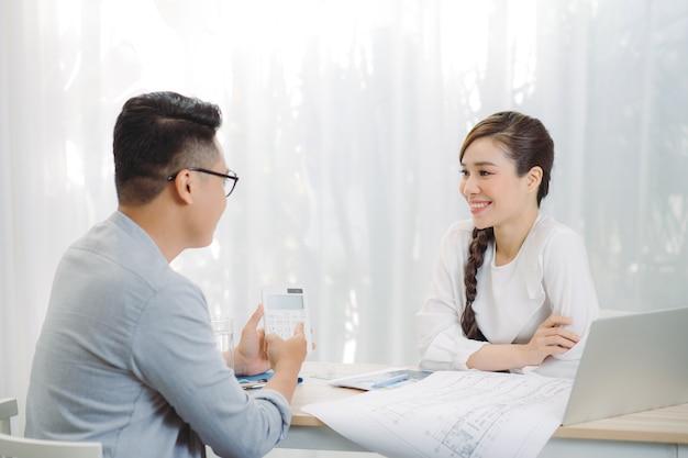 女性の不動産エージェントは、クライアントに住宅所有権と生命保険を提供しています。