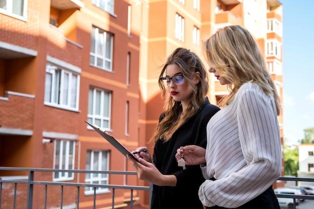クリップボードの鍵と屋外での販売のための家の近くの若い女性のクライアントを持つ女性の不動産エージェント