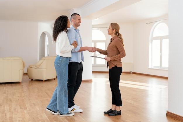 새 집 거래에 대 한 부부와 악수하는 여성 부동산