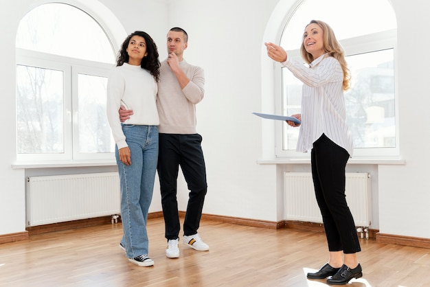 Female realtor showing young couple new house