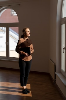 Female realtor standing in empty house and looking through the window